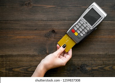 Pay by payment terminal. Woman's hand inserts credit card to terminal on dark wooden background top view copy space