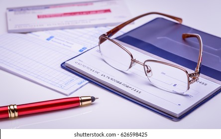 Pay with check instantly, on time. Glasses on a checkbook, red pen, financial documents on the background. Closeup, financial concept.