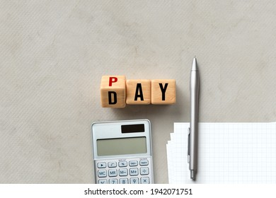 Pay Day concept with alphabet letters on wooden blocks, calculator and pen with notepaper conceptual of balancing expenditure against income