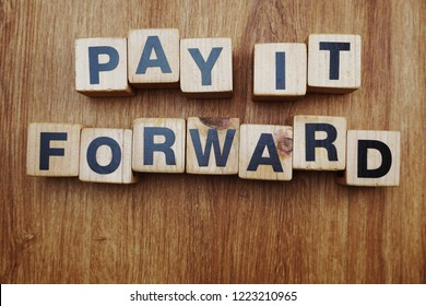 Pay It Forward alphabet letter on wooden background