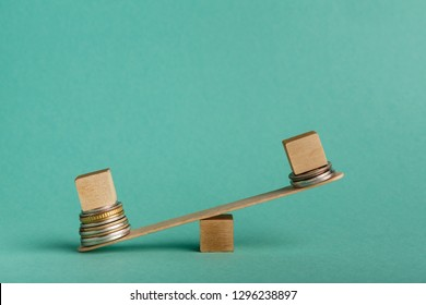 Pay gap and discrimination. Empty wooden cubes on seesaw with different stacks of coins, one outweigh, copy space