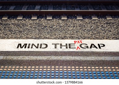 Pay gap, mind the pay gap graffiti inequality gap between employees pay concept – image