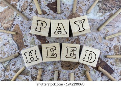 Pay Heed or Attention concept with alphabet letters on wooden cubes centred in a frame of small twigs over marbled stone background. Flat lay