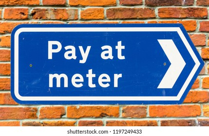 Pay At The Meter Arrow Sign Against Red Brick Wall, shallow depth of field Exeter Devon England Spring 2016