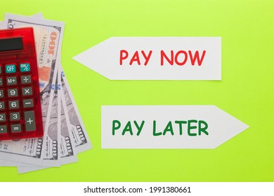 Pay Now or Pay Later written on paper arrow with hundred dollar bills and calculator. Business concept.