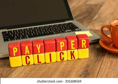 Pay Per Click written on a wooden cube in front of a laptop