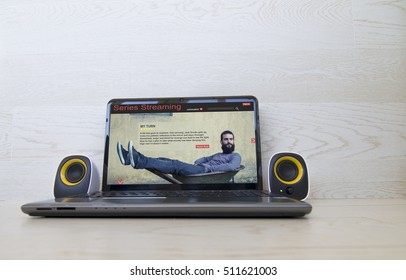 Pay per view concept: series streaming website on the screen of laptop and external speakers to the sides. All screen graphics are made up.