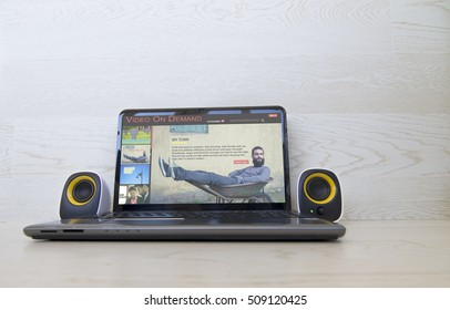 Pay per view concept: video on demand website on the screen of laptop and external speakers to the sides. All screen graphics are made up.