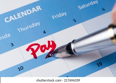 Pay word written on the calendar with a pen