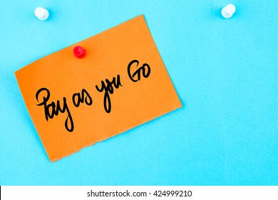 Pay As You Go written on orange paper note pinned on cork board with white thumbtack, copy space available