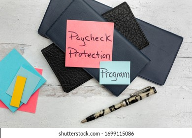 Paycheck protection program on posted notes sitting on a stack of check books