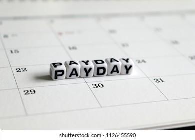 Awhitecubearrangedintheword 'PAYDAY'onthecalendar. Payday concept.