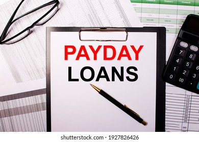 PAYDAY LOANS is written on a white sheet of paper, near the glasses and the calculator.