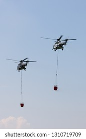 Payerne, Switzerland - September 5, 2014: Swiss Air Force Aerospatiale AS332 (TH89) military utility helicopters T-320 and T-316 flying with bambi buckets for aerial fire fighting.