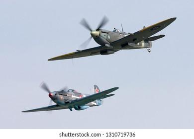 Payerne, Switzerland - September 5, 2014: Supermarine Spitfire Mk16e World War II fighter aircraft G-MXVI flying in formation with Yakovlev Yak-3M.