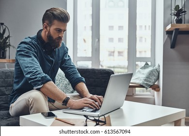 Paying attention to every detail. Thoughtful young modern man using computer while sitting at his working place