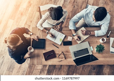 Paying attention to every detail. Top view of young modern colleagues in smart casual wear working together while spending time in the office