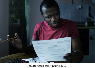 Paying bills concept. Stressed african American man do not understand great sums in his bills, checking accounting, not able to believe these numbers are true, looking for some mistake