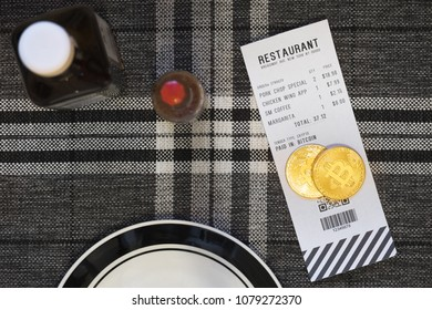 Paying with Bitcoin or other crypto currency at a restaurant - A wide shot Bitcoin on top of a receipt in a restaurant setting.