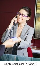 Paying by credit card: young salesclerk smiling at a customer