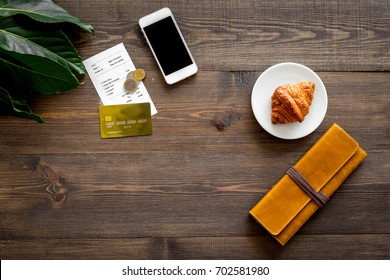 Paying at cafe by card. Bill and coins near croissant and wallet on dark wooden table top view copyspace