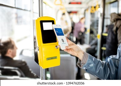 Paying conctactless with smartphone for the public transport in the tram, close-up view