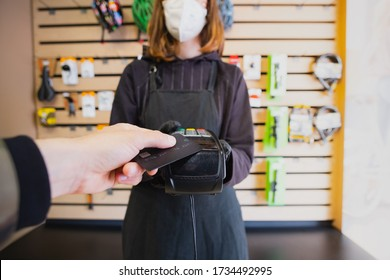 Paying with a credit card at a small local shop. Store assistant holding payment terminal at a bike shop, point of view shot
