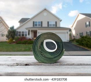 Paying house by cash concept with a big roll of banknotes against blurred house background