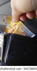 paying with ten swiss francs from a wallet