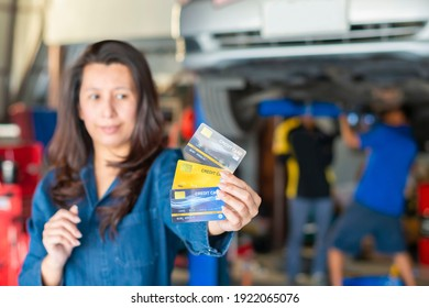 Payment by credit card. Customer asian woman show many credit card at auto repair shop. Focus on hand and credit card