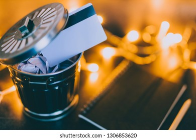 payment card thrown in the trash next to notepad with pencil and fairy lights bokeh,  concept of learning to spend less and better budgeting