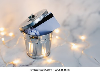 payment card thrown in the trash surrounded by fairy lights on marble desk, concept of learning to spend less and refrain from excessive shopping
