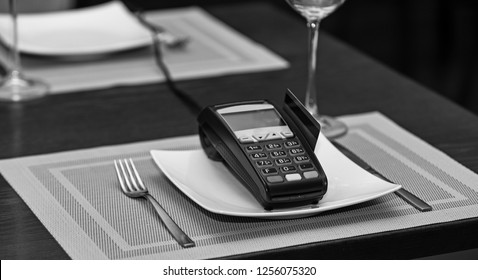 Payment with credit card. Credit card terminal near glasses and plates on table background. Credit card payment and electronic bank concept. EDC machine or bankcard in reader on table in restaurant.