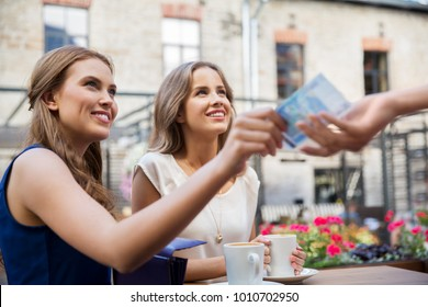 payment, finances and people concept - smiling young women paying for coffee with cash money at street cafe
