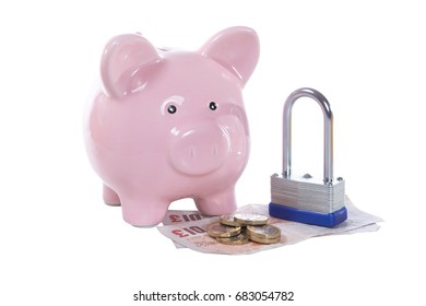 Payment or financial security concept with a pink piggy bank and padlock isolated on white on top of a pile of pound coins and bills