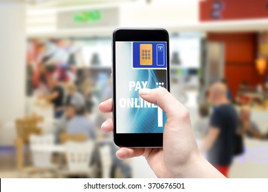 Payment on line with your cellphone. Woman pays the phone in the blurry background inside the store.