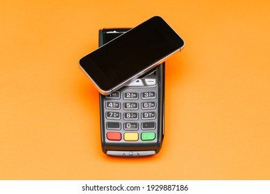 Payment for purchases with a mobile phone. Payment terminal and smartphone. Contactless payment for goods. E-commerce and business.