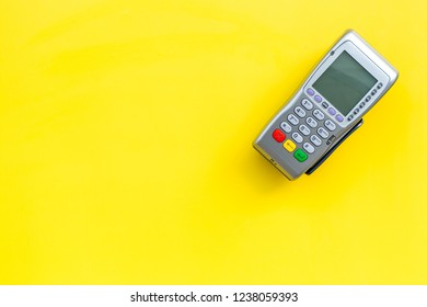 Payment terminal, compact POS terminal on yellow background top view space for text