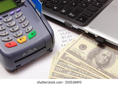 Payment terminal with credit card, money, laptop and financial calculations, credit card reader, finance concept