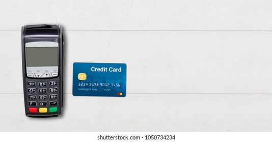 Payment terminal and credit card on wooden background copy space for web banner concept