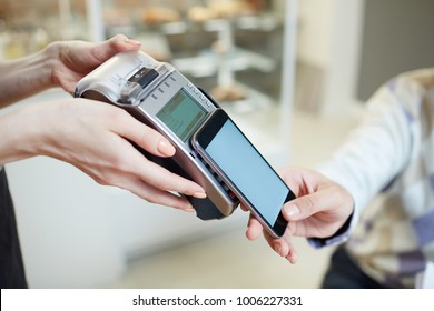 Payment terminal held by waitress and smartphone of client over its keypad during transaction