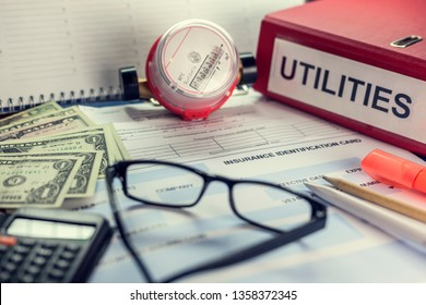 """Payment of utilities for electricity and water: receipt, bills and a calculator. On the folder the inscription """"Utilities"""""""