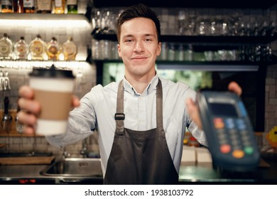Payment via the bank's nfs terminal. Modern uniform apron in the restaurant. A satisfied barista brews and sells coffee to take away. Paper cup with a drink Americano, espresso, cappuccino.