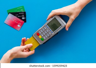 Payments in shops. Hand insert bank card in terminal on blue background top-down