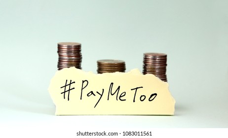 #PayMeToo as a new campaign to close the wage gap between men and women. Handwrittenletter#PayMeTooontornpaperwithpileofcoins.