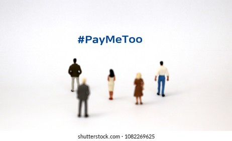 #PayMeToo as a new campaign to fill the wage gap between men and women. Aminiaturemanandaminiaturewomanstandingonapieceofpaperwith#PayMeTooonit.