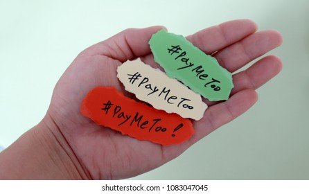 #PayMeToo as a new movement. #PayMeToo written as torn paper on palm.