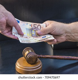payoff concept/on hand gives bank notes to another hand and judge gavel with sound block on a black background