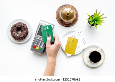 Paypass tech. Contactless payment. Woman's hand brings the bank card to payment terminal near bill, service bell, coffee on white stone background top view copy space