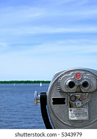 Pay-per-view binoculars look out over a pretty lake with sailboats in the far distance